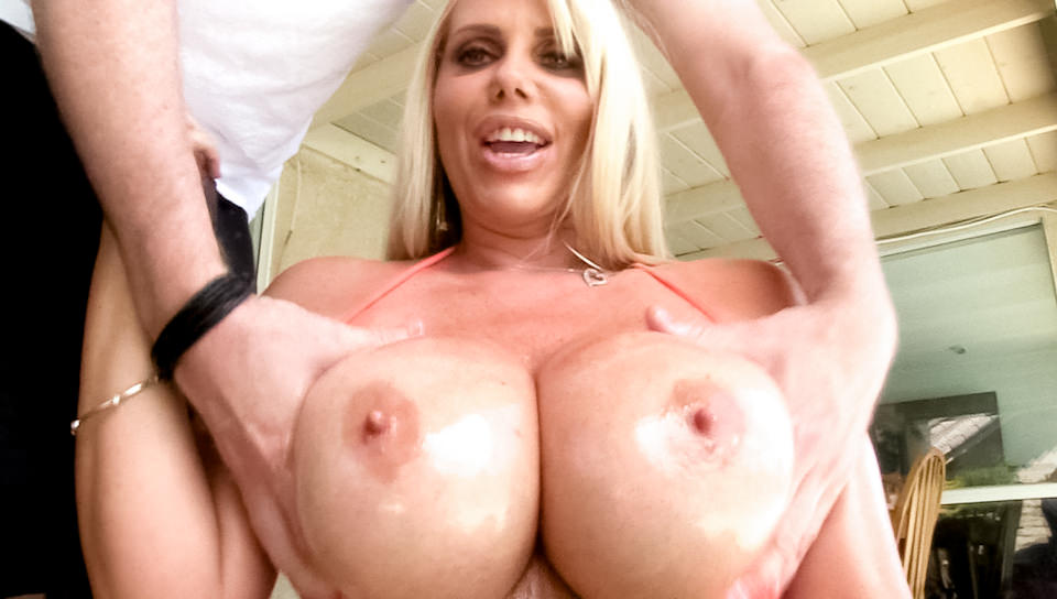 She is rubbing her shiny tits against one pink raging dick
